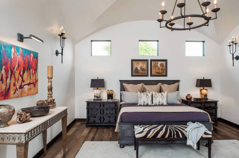 White bedroom decorated with gorgeous artworks and a wrought iron chandelier that hung from the arched ceiling. It has a console table and a dark wood bed that complements the custom nightstands topped with sleek table lamps.