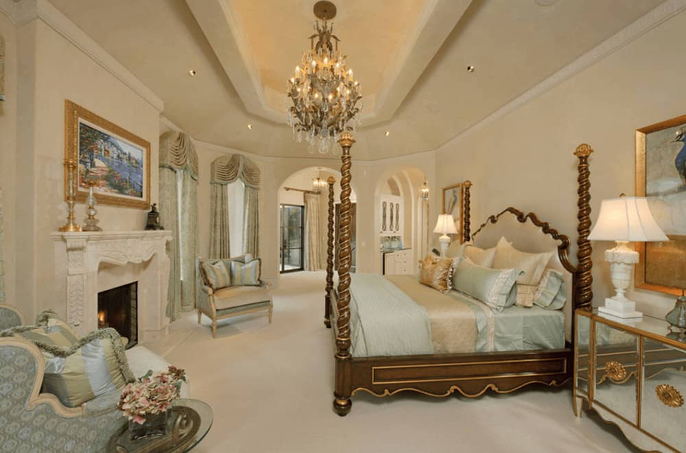 Blue patterned armchairs sit in front of the ornate fireplace that's accented with a lovely landscape painting. This luxury bedroom has a gorgeous four poster bed and mirrored nightstands lighted by white table lamps.