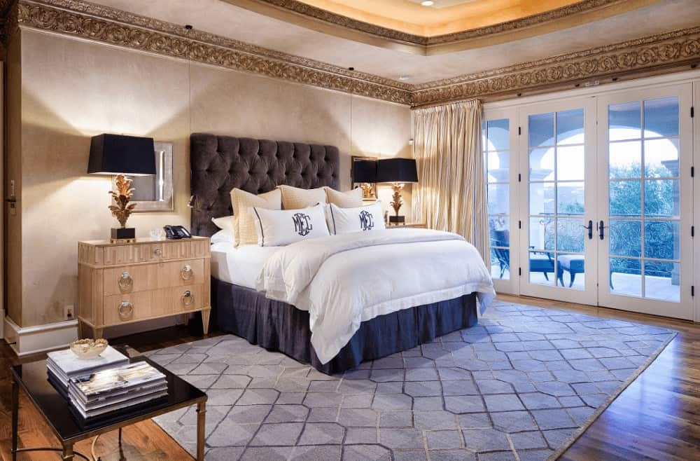 Sophisticated bedroom with a tufted bed on a patterned rug and wooden nightstands topped with stylish table lamps. It has a French door and paneled walls lined with ornate crown molding.