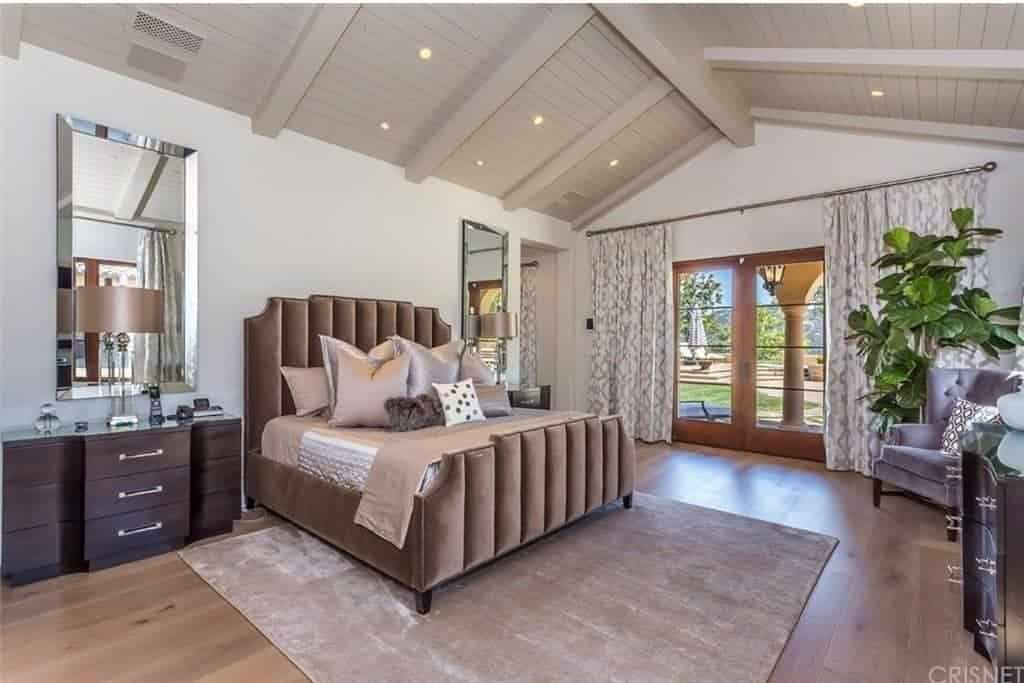 A fiddle leaf fig plant in the corner creates a refreshing ambiance in this bedroom with wood beam ceiling and a French door that leads out to the lush green garden. It has a classy velvet bed and wooden nightstands paired with beveled mirrors.