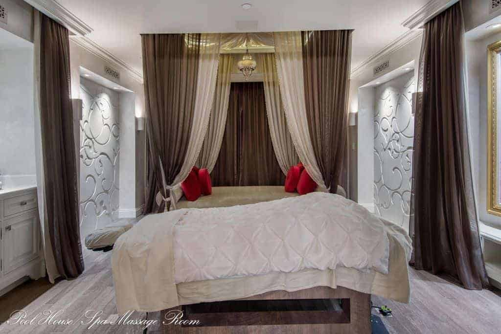 Flowy white and brown sheer curtains add character in this elegant bedroom with ornate inset walls and a gorgeous canopy bed accented with red pillows.