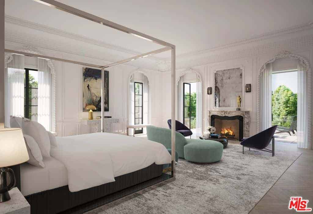 Light and airy bedroom with a mirrored canopy bed and a cozy seating area by the ornate fireplace. It has chevron wood flooring and glazed windows inviting natural light in.