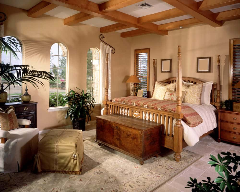 Fresh bedroom boasts a wooden four poster bed and a white armchair paired with a skirted ottoman. It has arched windows and limestone flooring topped by a classic area rug.