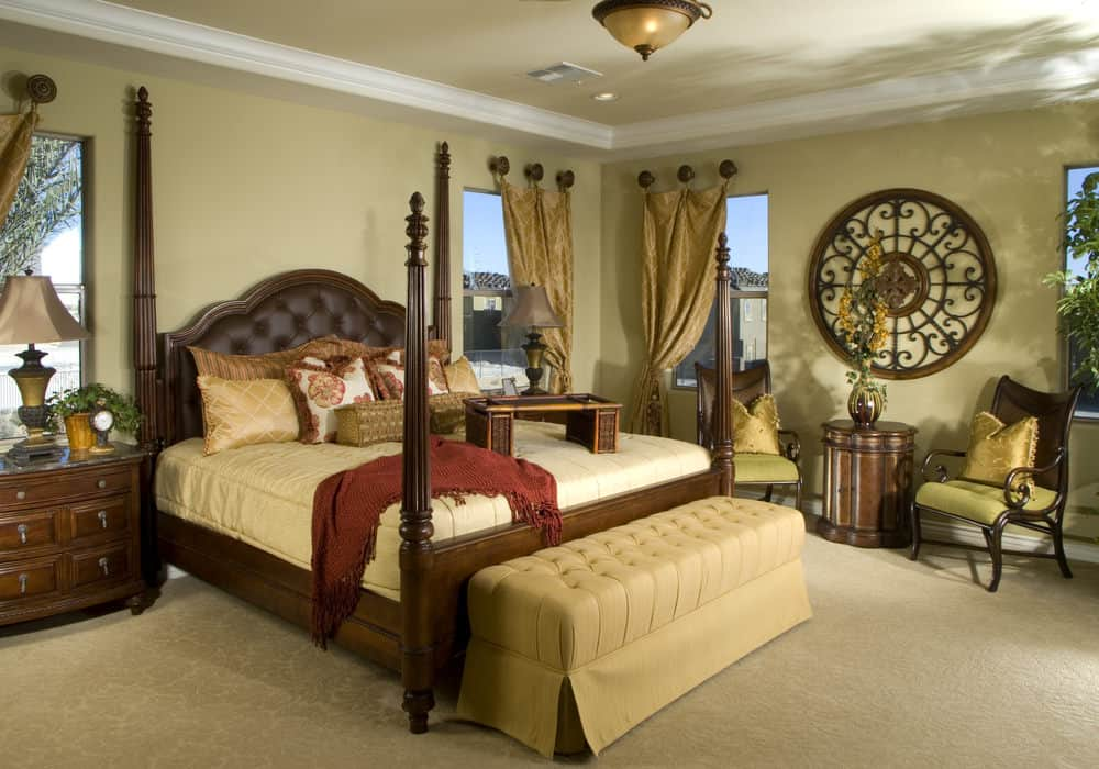 Classic bedroom showcases a four poster bed with a beige tufted bench on its end along with a seating area on the side accented with round ornate wall art.