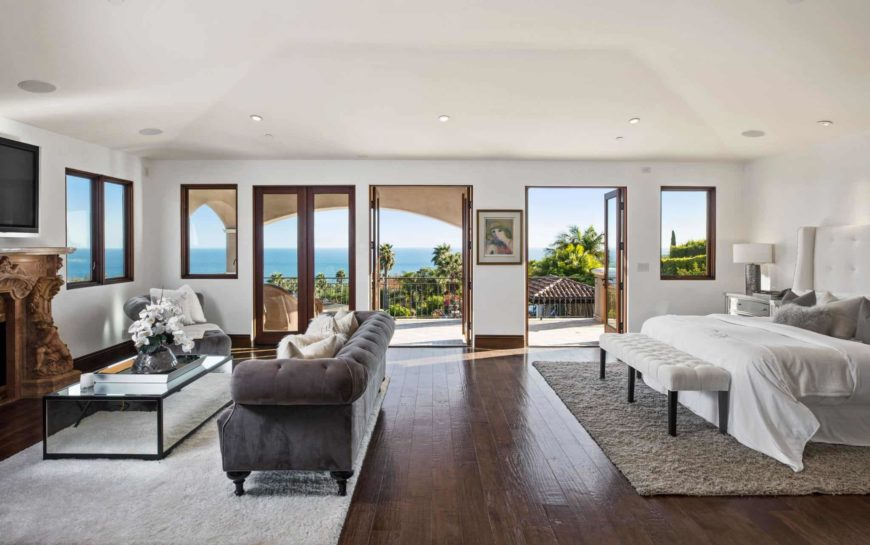 Spacious bedroom with wide plank flooring and glazed windows and doors overlooking a breathtaking ocean view. It has a white wingback bed and gray tufted sofa facing the glass top coffee table and carved wood fireplace.
