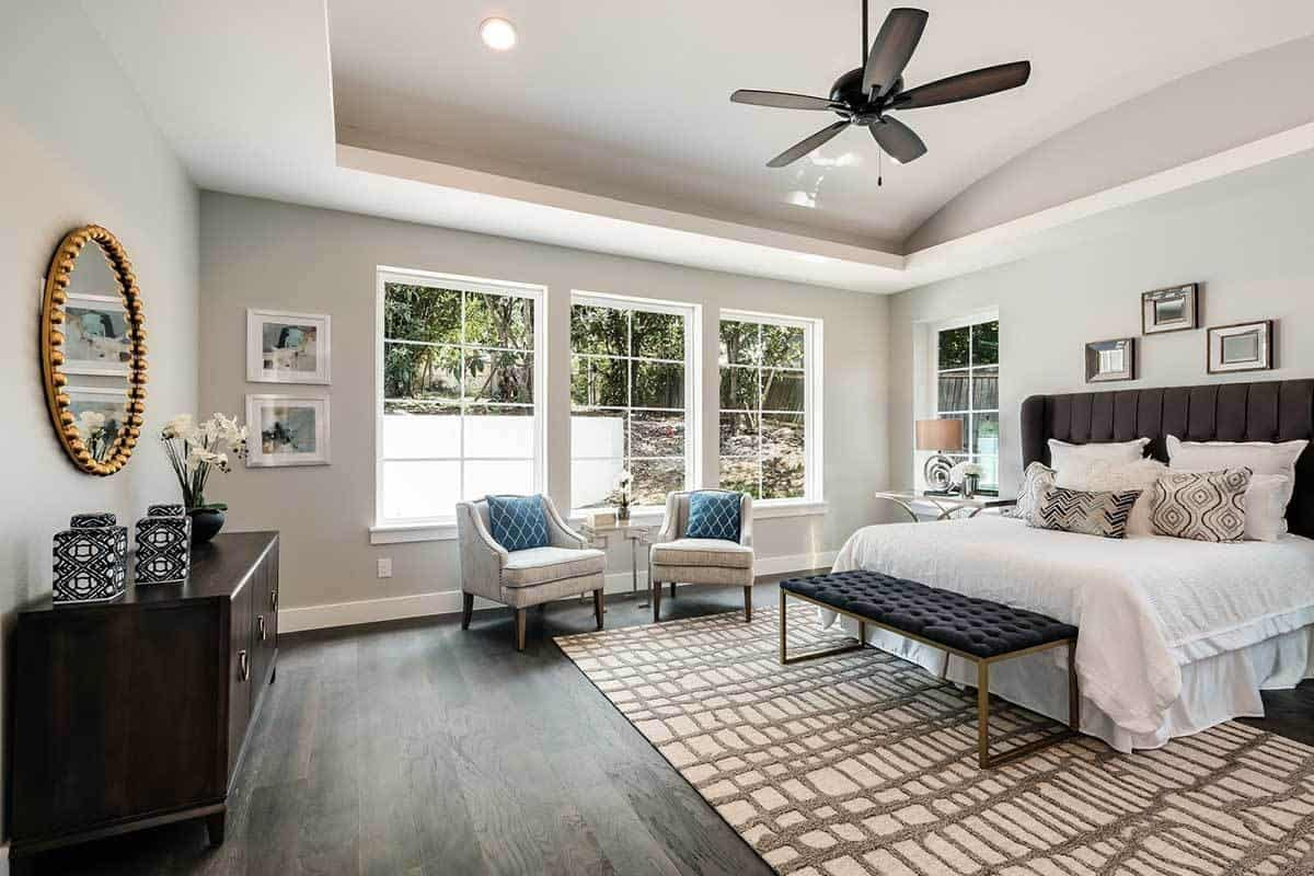 A dark brown ceiling fan contrasts the light gray cove ceiling that it hangs from. This light gray hue extends to the walls that are brightened by the wide windows and contrasted by the dark cushioned headboard matching the cushion of the bench at the foot of the bed.