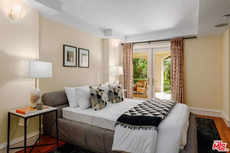 This bedroom has a cozy and comfortable gray platform bed with a white cushion that complements the beige walls and white tray ceiling. These walls and ceiling are accented with wall-mounted lamps and table lamps that are flanking the bed.