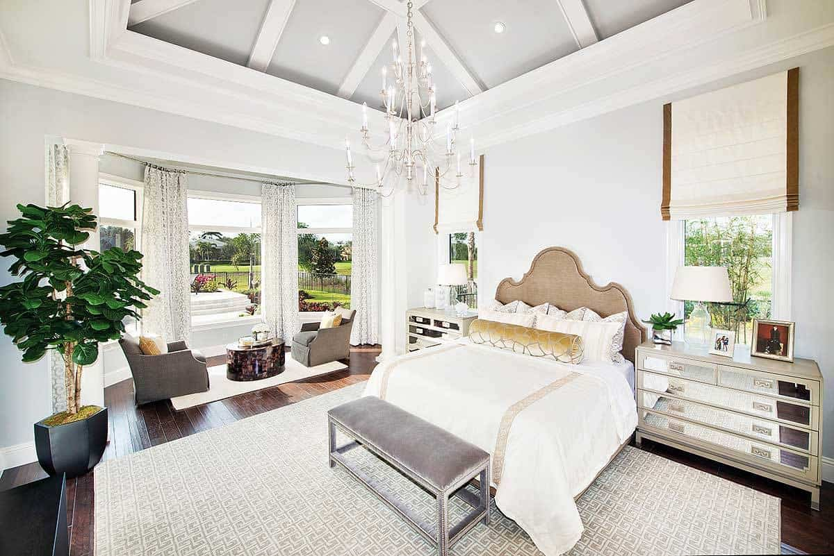 The light gray cathedral ceiling hangs a majestic and bright white chandelier. This brightness matches with the bright white walls that make the unique design of the headboard stand out. This also goes well for the mirrored bedside drawers that reflect the brightness onto the patterned area rug.