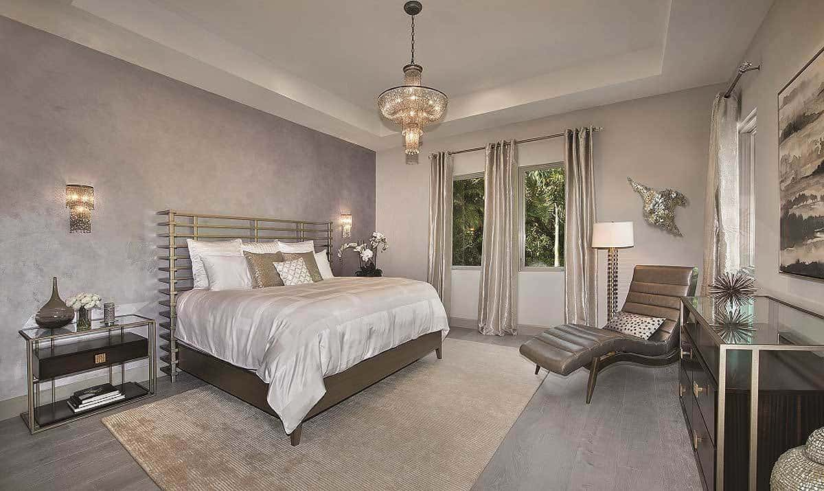 The platform bed of this Mediterranean-style bedroom has a unique metal headboard with grills. This unique feature is paired with various other metallic and silvery decors and elements in the bedroom that goes well with the gray walls and gray flooring.