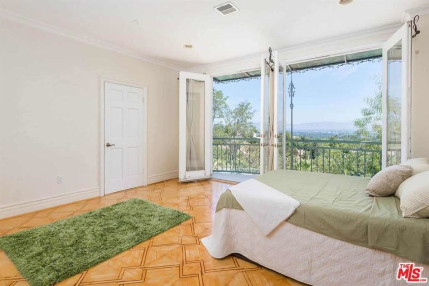 The green furry area rug that stands out against the orange hardwood flooring with patterns matches with the green bed sheet of the traditional bed. This is brightened by the open glass doors on the side that showcase the wonderful green treetops view.