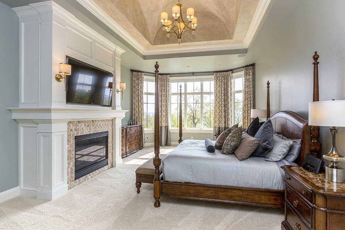This Mediterranean-style bedroom has a fireplace embedded into a large wooden column with an elegant finish that also houses the TV. This is across from the wooden pencil poster bed with a matching wooden headboard that matches with the bedside drawers.