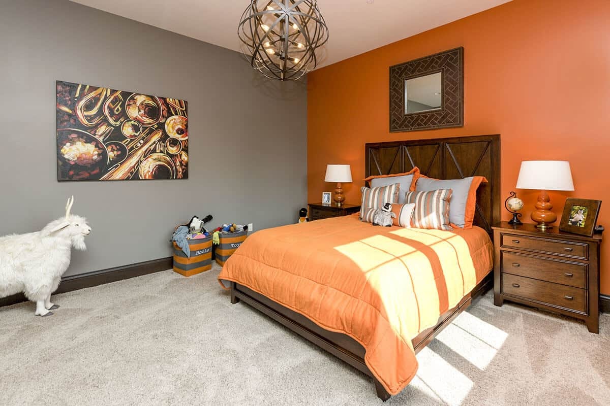 This Mediterranean-style bedroom has two tones. The first one is the bright orange hue that can be seen on the bed sheets and pillows matching the wall behind the wooden headboard. The other is the gray wall that matches with the gray carpeted flooring.