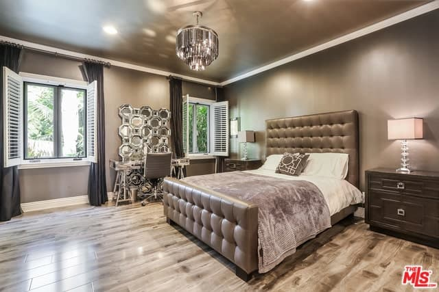 This Mediterranean-style bedroom has a crystal chandelier that pairs well with the patterned mirror panel at the vanity area in between the two shuttered windows beside the tufted brown leather sleigh bed with a large headboard.