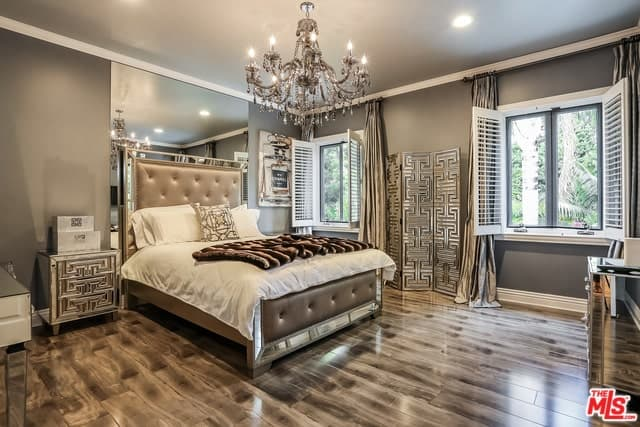 The gray walls and hardwood flooring of this master bedroom pairs well with the bedside drawers and the room divider that both have metallic patterns. This matches with the mirrored lining of the bed frame that has a dark brown cushion.