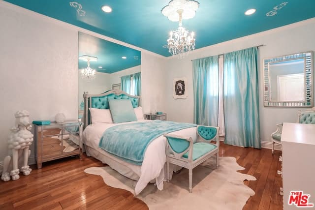The ceiling of this Mediterranean-style bedroom has a light blue hue that matches with the blue cushion of the headboard and the bench at the foot of the bed. This also matches with the blue curtains of the window that contrasts the light gray walls and hardwood flooring.