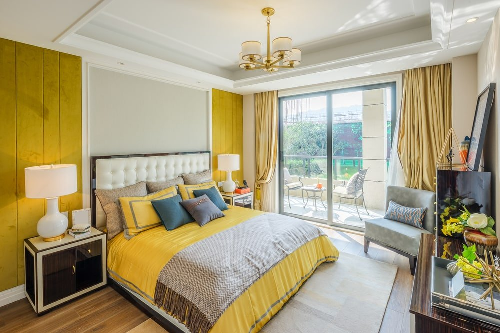 The cheerful mustard yellow sheets of the traditional bed matches with with its pillows and the two wooden wall panels behind the sleek black bedside drawers that bears table lamps. These lamps match with the design of the chandelier hanging from the white tray ceiling.