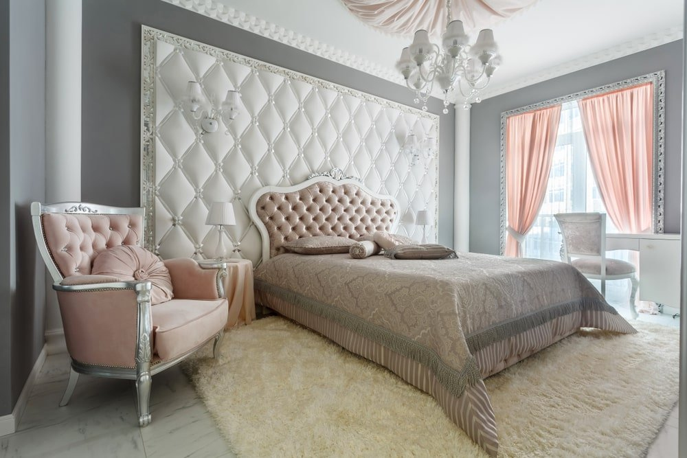 This chic master bedroom has a rose pink tufted headboard that makes it stand out against the large white cushioned panel behind it with matching white wall-mounted lamps that mirror the design of the chandelier above that hangs from the white ceiling with a pink cloth in the middle.