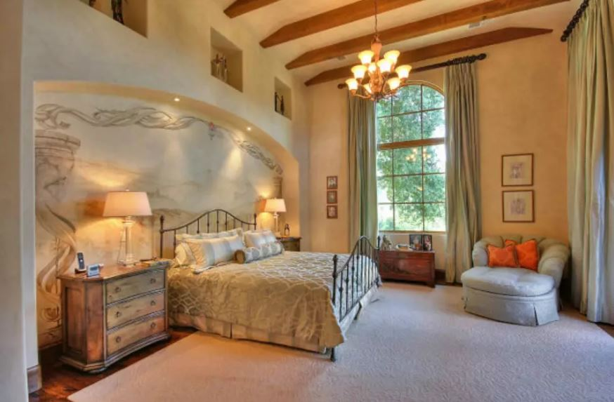 The high ceiling that has exposed wooden beams and the tall arched window of the beige wall are both complemented by the large warm chandelier. This matches with the two table lamps that illuminate the beautiful alcove of the wrought iron bed.
