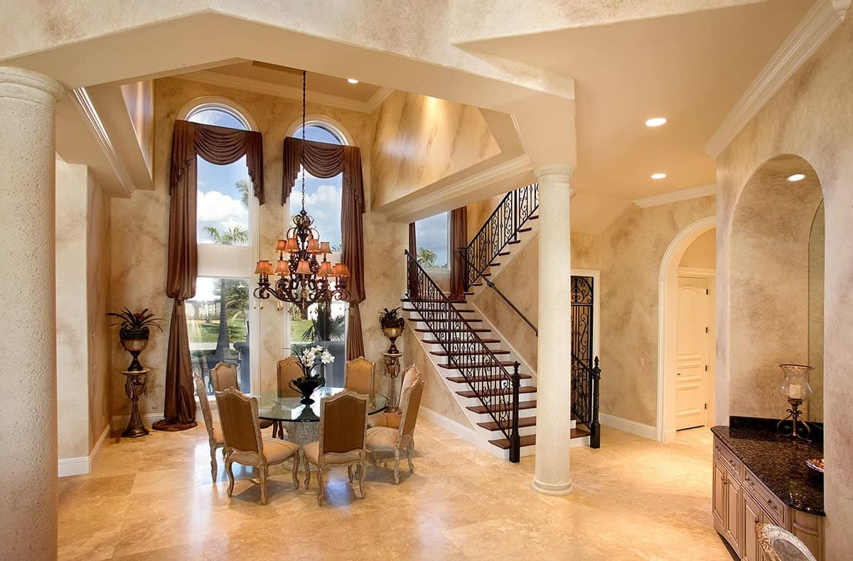 This is an elegant Mediterranean-style dining room beside the stairs and a tall white pillar. The high ceiling is augmented by tall arched windows with brown curtains that match the cushions of the dining chairs around the glass-top round table.