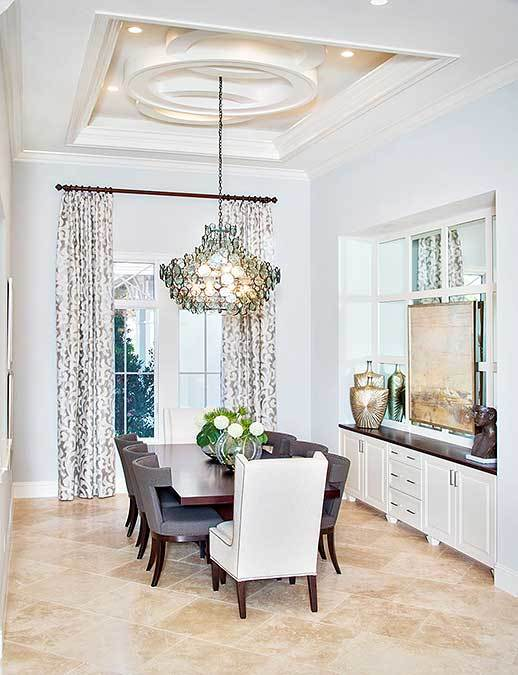 The white tray ceiling has unique designs on its central tray that hangs a decorative chandelier over the centerpiece of the dark wooden table. This is complemented by the beige marble tiles of the floor as well as the built in dining room cabinet on the side that bears decors.