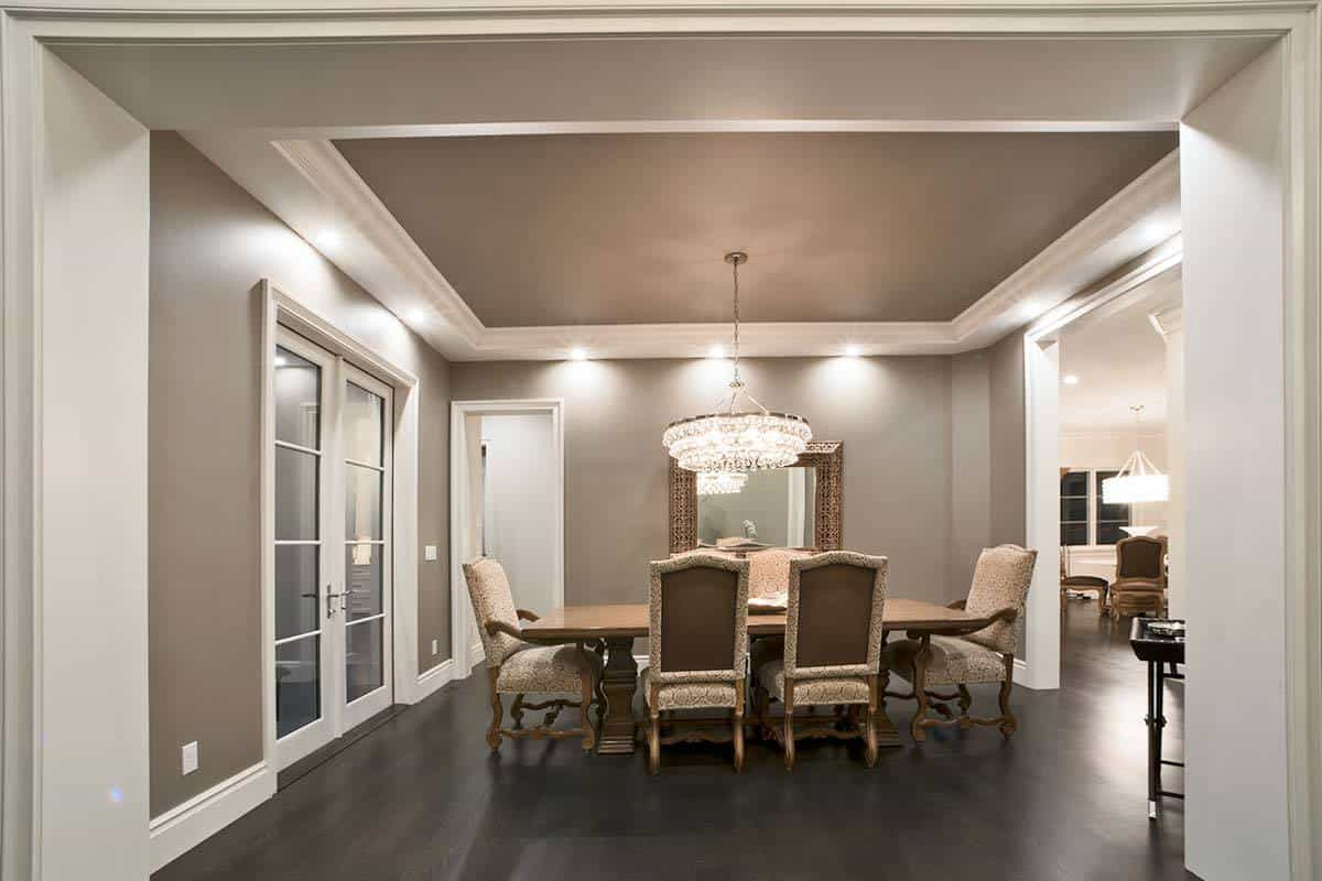 This simple dining room has a gray ceiling that matches with the walls and lined with white moldings that matches the white frames of the glass doors brightened by the brilliant chandelier. This is contrasted by the dark hardwood flooring that makes the brown dining set stand out.