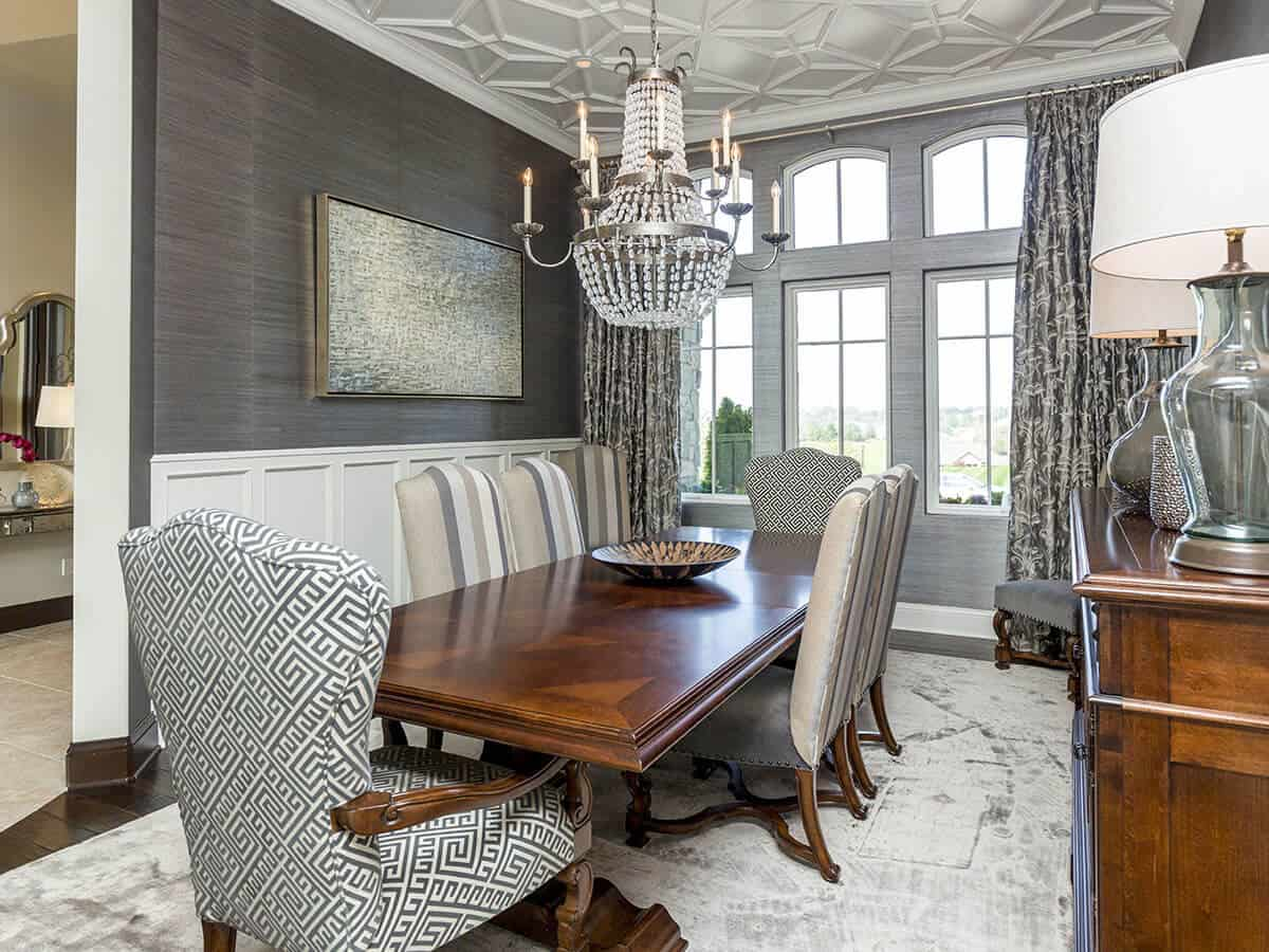 The white ceiling is dominated by unique patterns that goes well with the patterned cushions of the armchairs at the ends of the wooden dining table. This stands out against the white wainscoting and gray walls that are brightened by the tall arched windows.