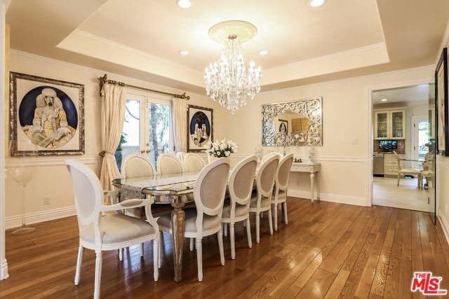 The bright white decorative chandelier brightens the beige tray ceiling and walls that are adorned with colorful paintings and a mirror mounted by the head of the sleek golden dining table. This is surrounded by elegant beige oval-back chairs.