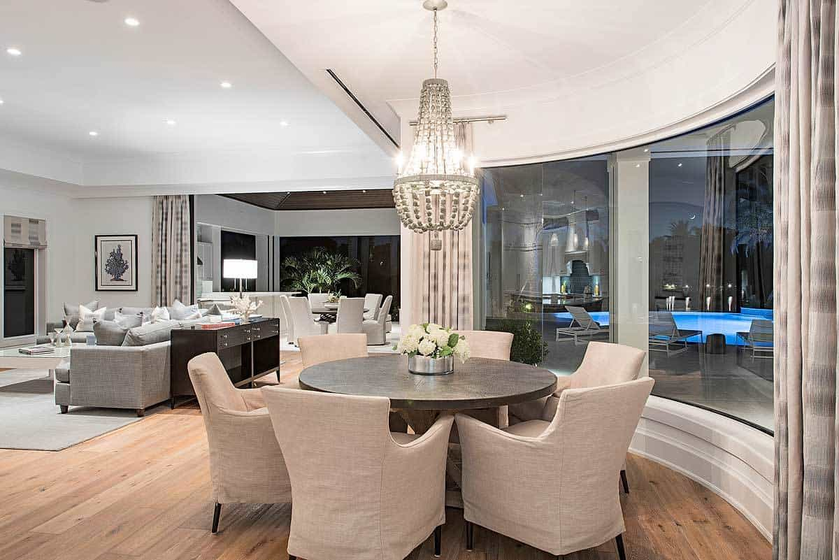The brilliant white decorative chandelier hanging from the white ceiling casts a brilliant white light over the dark brown round dining table that is complemented by the beige slipcovers of the armchairs around it. This is given a nice background of a curved glass wall.