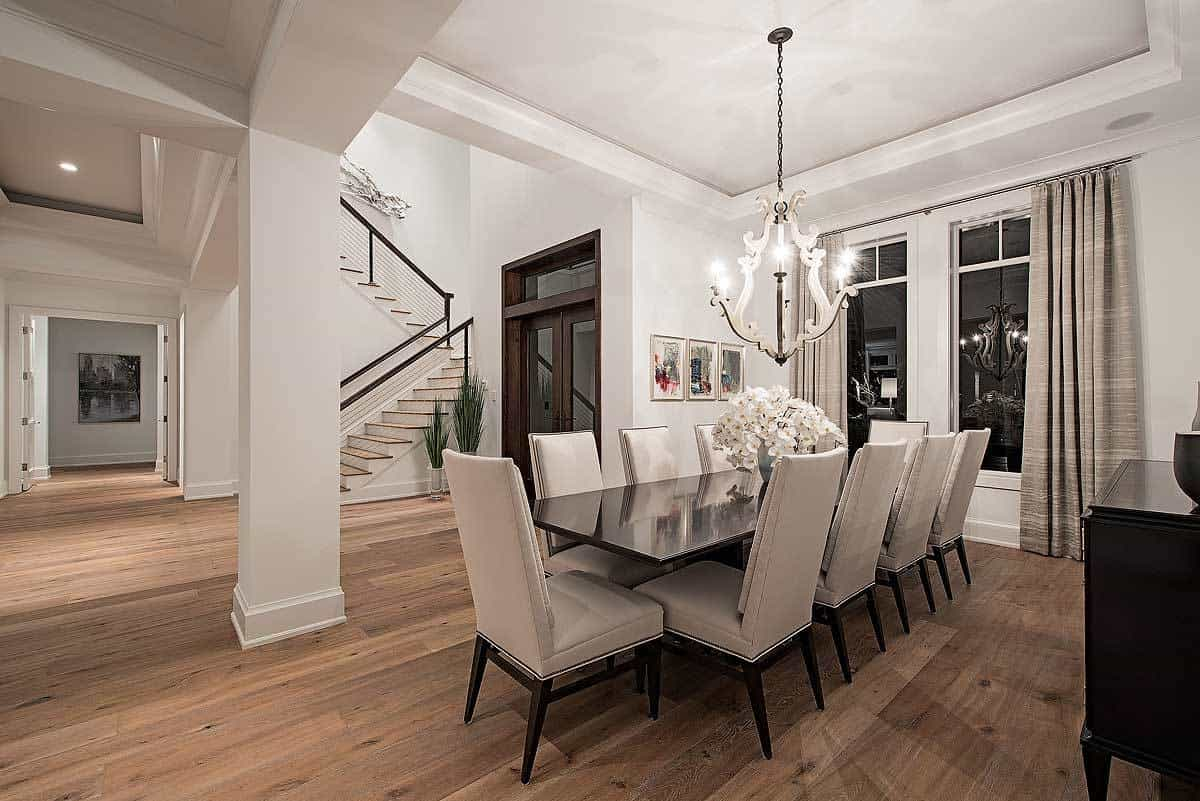 This charming Mediterranean-style dining room has a long black wooden dining table that matches the black wooden legs of the light gray cushioned chairs. These are brightened by the white walls, pillar and a white tray ceiling that hangs a brilliant chandelier.
