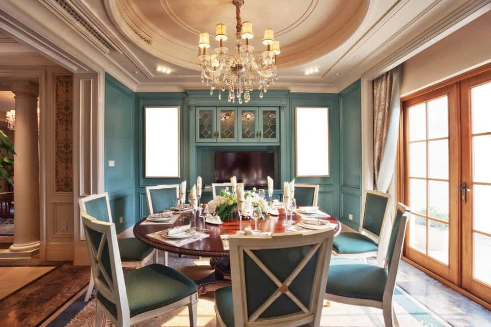 The elegant design of the ceiling has a central circular tray that supports a crystal chandelier over the dark wooden round table that has dining chairs with green cushions on its white wooden frames. They match the hue of the wall with an elegant finish.