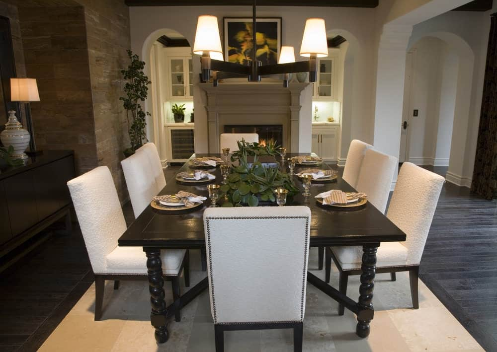 The white textured cushions of the dining chairs make them stand out in contrast to the dark wooden dining table with elegant designs on its legs. The table pairs well with the frame of the simple chandelier that casts off yellow light complementing the classic painting over the fireplace.