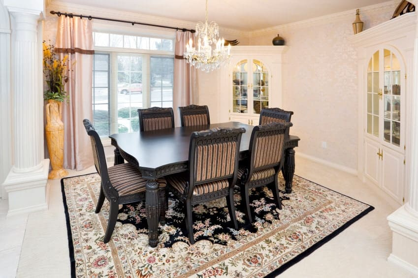 The light pink wallpaper of this Mediterranean-style dining room has subtle details that go well with the pink patterned area rug under the black wooden dining set. This is illuminated by the small crystal chandelier as well as by the large windows.