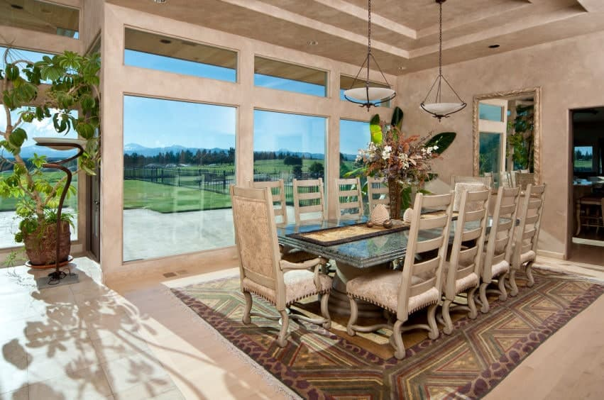 The colorful patterned area rug is a nice complement to the light hardwood flooring that blends well with the walls and the tray ceiling that hangs two dome pendant lights over the large dining table surrounded by light pink chairs.