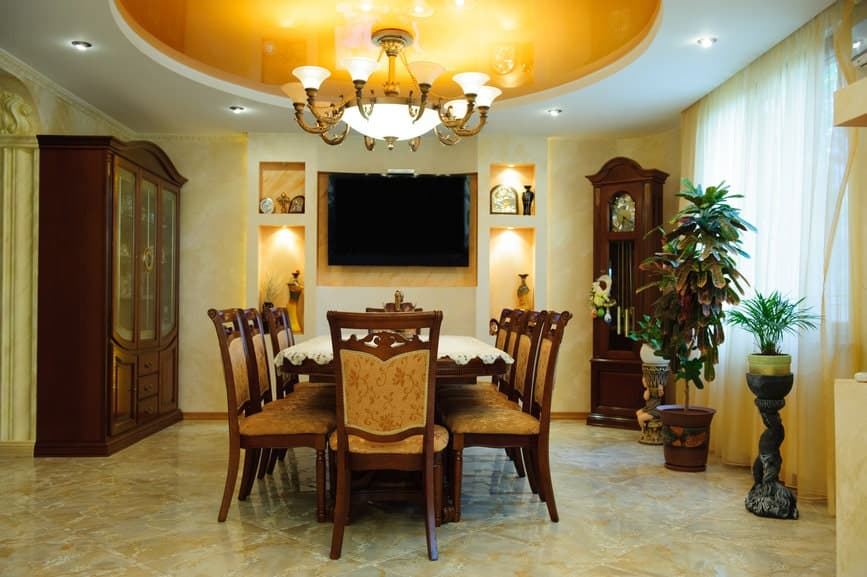 This Mediterranean-style dining room has yellow flecks to its marble flooring that complements the yellow tint of the circular middle tray of the ceiling. This matches with the wall by the head of the table that houses the TV and some decors on its built-in shelves.