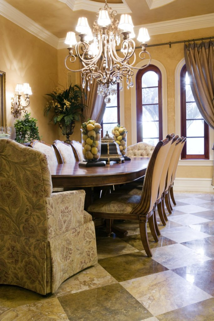 The checkered marble flooring of this elegant Mediterranean-style dining room matches the subtle floral patterns on the slipcovers of the dining chairs that also fit well with the intricate design of the chandelier above the wooden dining table.