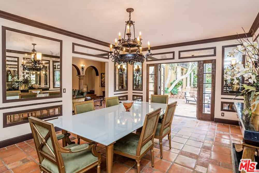 The two-tier chandelier has a dark brass finish to it that goes well with the dark wooden molding of the beige ceiling and walls. This makes the white glass top table stand out that also contrasts the terracotta flooring and light green chairs.