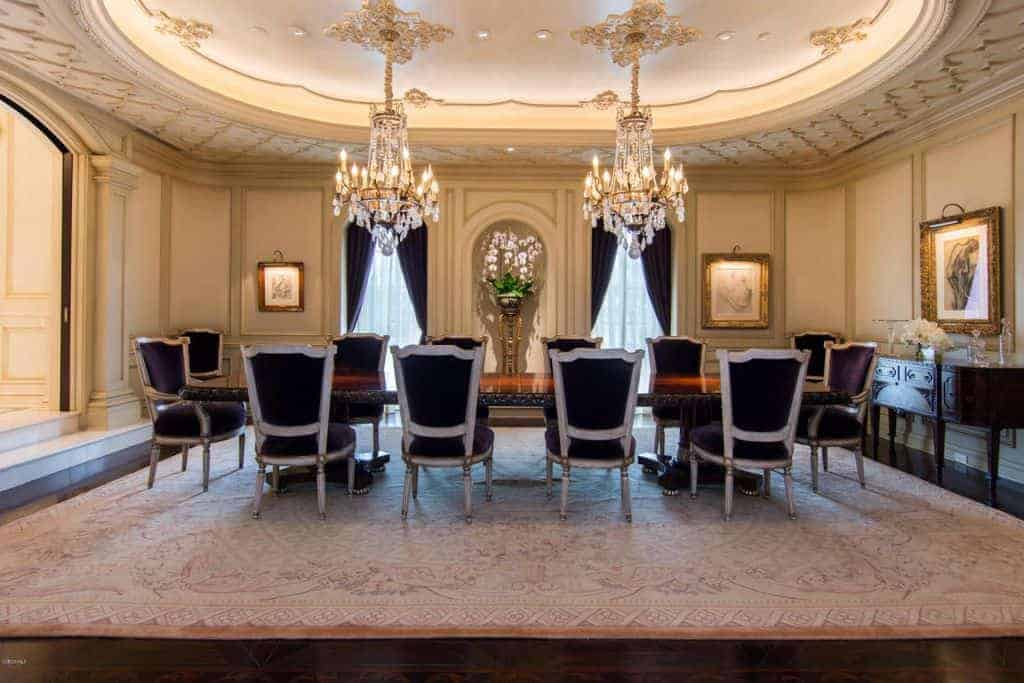 The long wooden dining table of this formal Mediterranean-style dining room is big enough for two majestic crystal chandeliers hanging from a large elegant light pink ceiling that blends with the walls and the large patterned area rug covering most of the dark hardwood flooring.