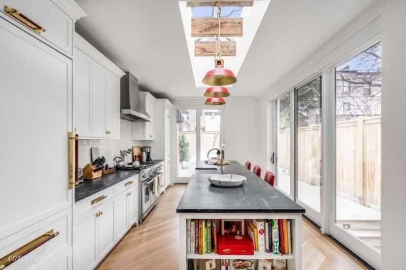 A single wall kitchen with a ceiling with skylights and hardwood flooring. The kitchen offers a long center island with built-in shelving along with a black countertop.