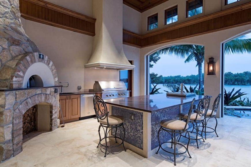 A spacious outdoor kitchen featuring a large stone oven and a massive center island with classy chairs, set under the home's tall ceiling.