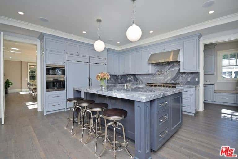 A blueish gray kitchen with a stunning backsplash and a massive center island featuring a gorgeous countertop, lighted by pendant lights.