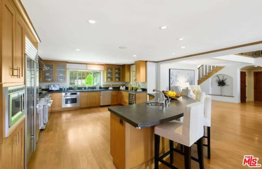 Spacious kitchen with a curved breakfast bar island featuring a black countertop paired with white chairs.