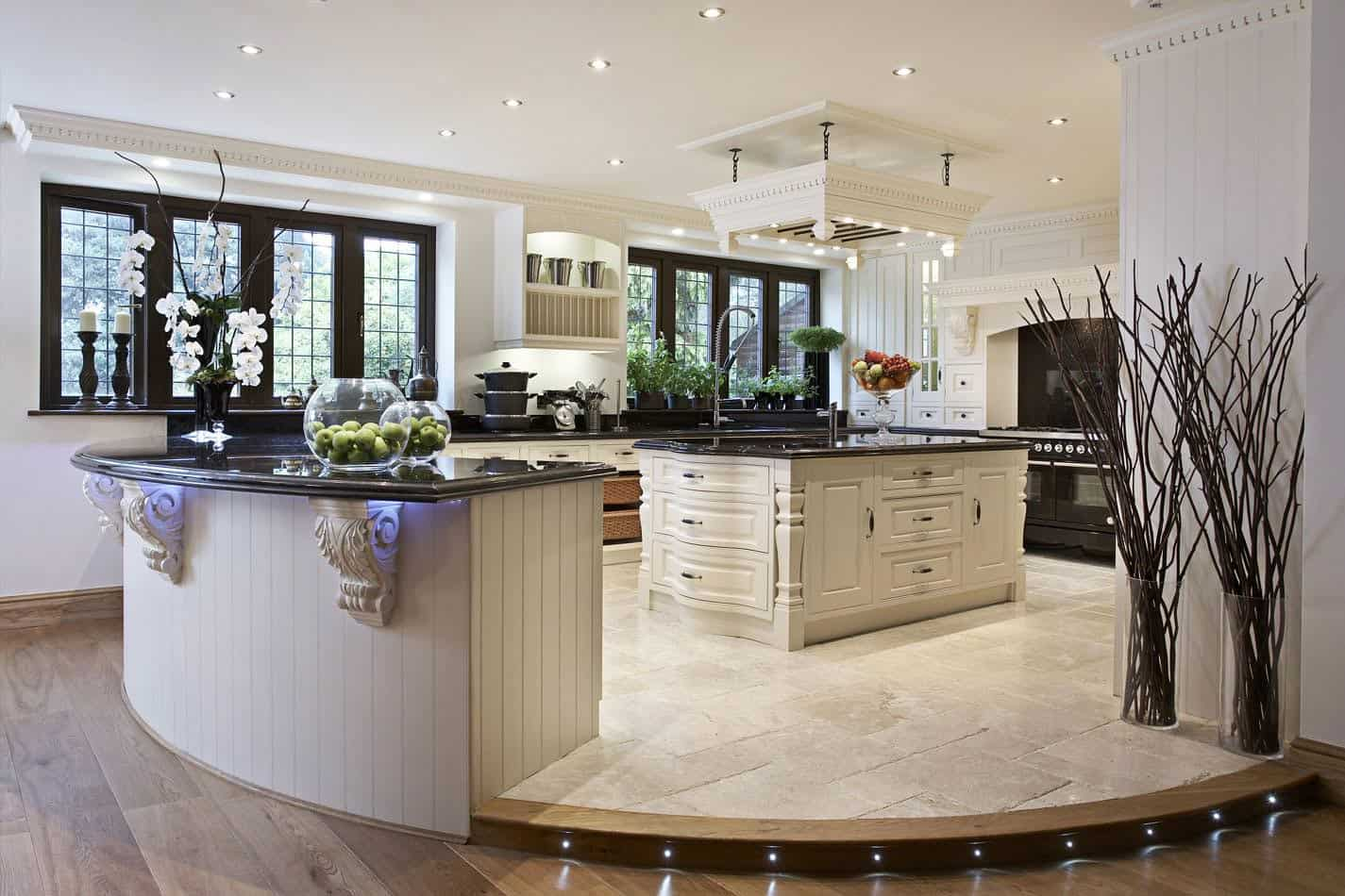 A gorgeous kitchen setup boasting a beautiful design and elegant black countertops lighted by recessed ceiling lights.