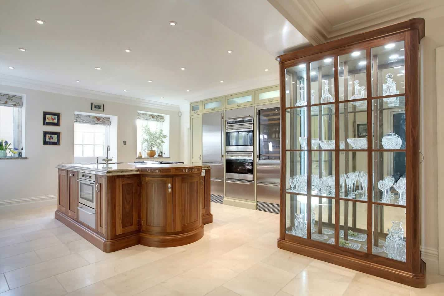 A spacious kitchen featuring a stunning glass cabinet with built-in lights, along with a large brown center island. The area is lighted by well-placed recessed ceiling lights.