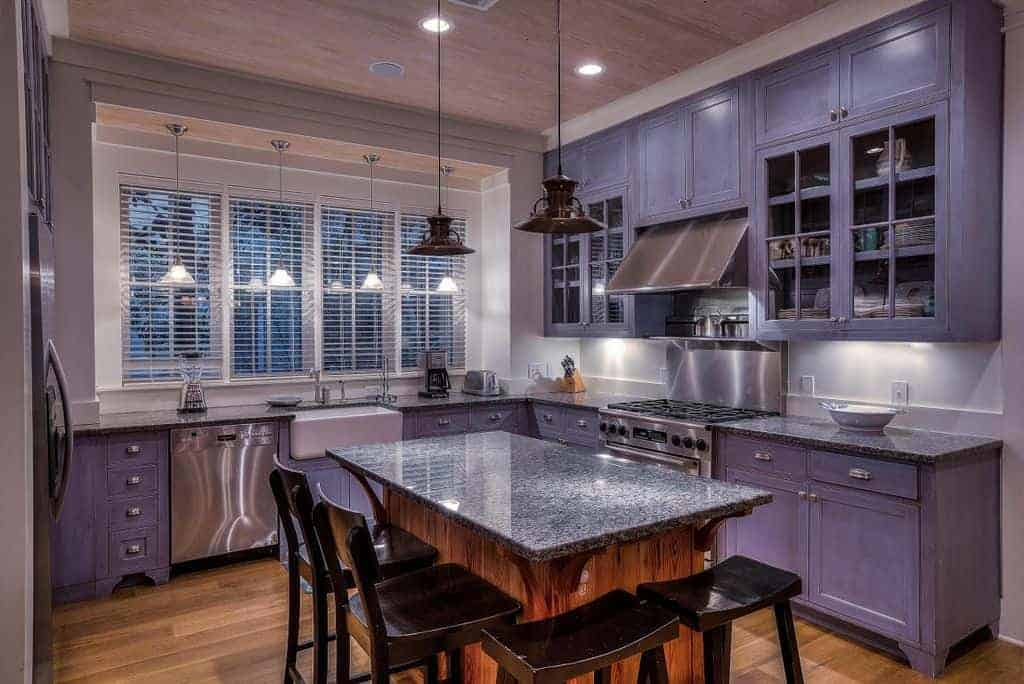 This kitchen features purple kitchen cabinetry and kitchen counters. The area also offers a center island with a granite countertop, lighted by two pendant lights.