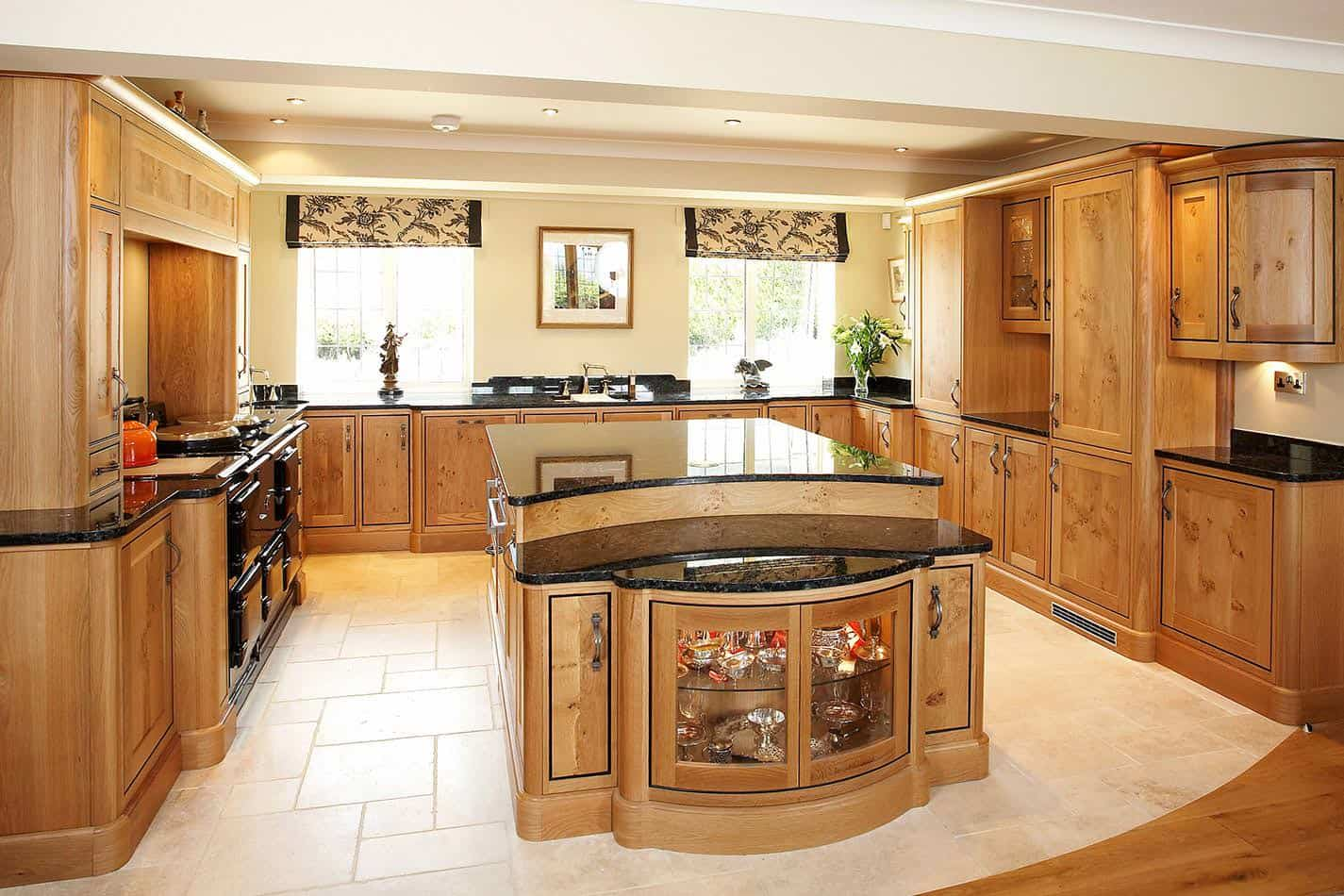 A brown U-shaped kitchen with a large center island with built-in shelving and cabinetry. The counters and the island boast black marble countertops.