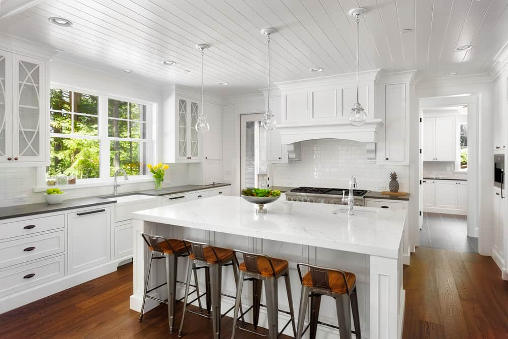 A white kitchen with hardwood flooring. It features an all-white center island with space for a breakfast bar lighted by pendant lights.
