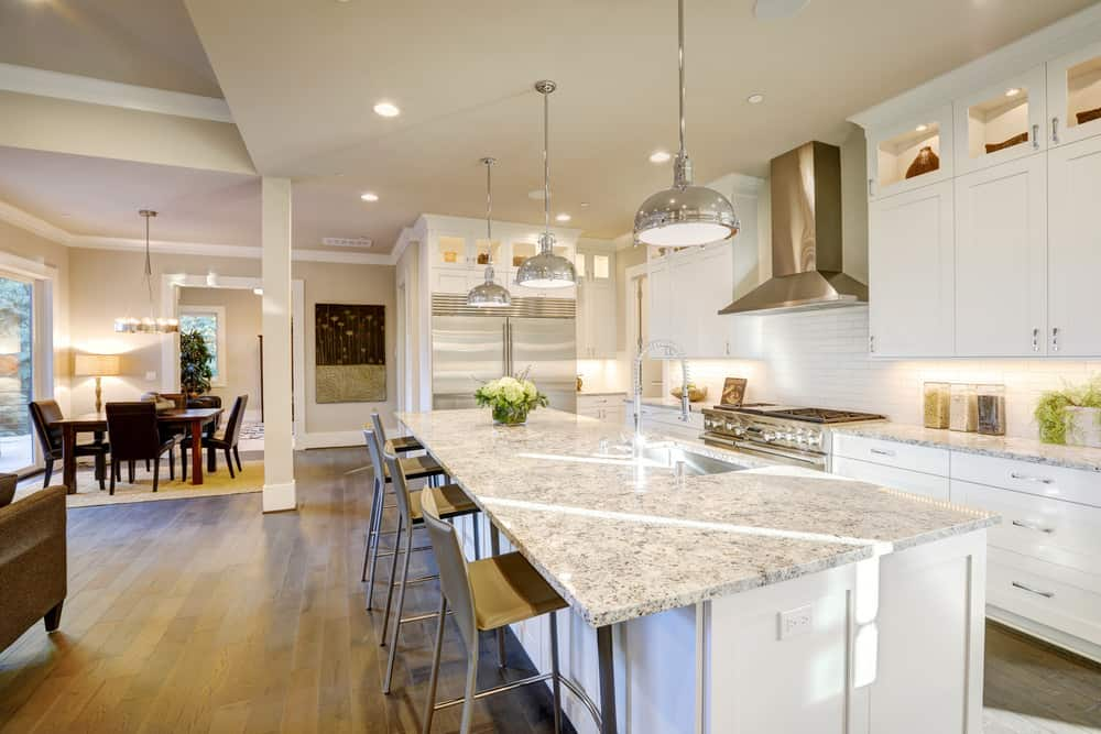 This kitchen features white cabinetry and kitchen counters, along with a long center island featuring a marble countertop lighted by three pendant lights.