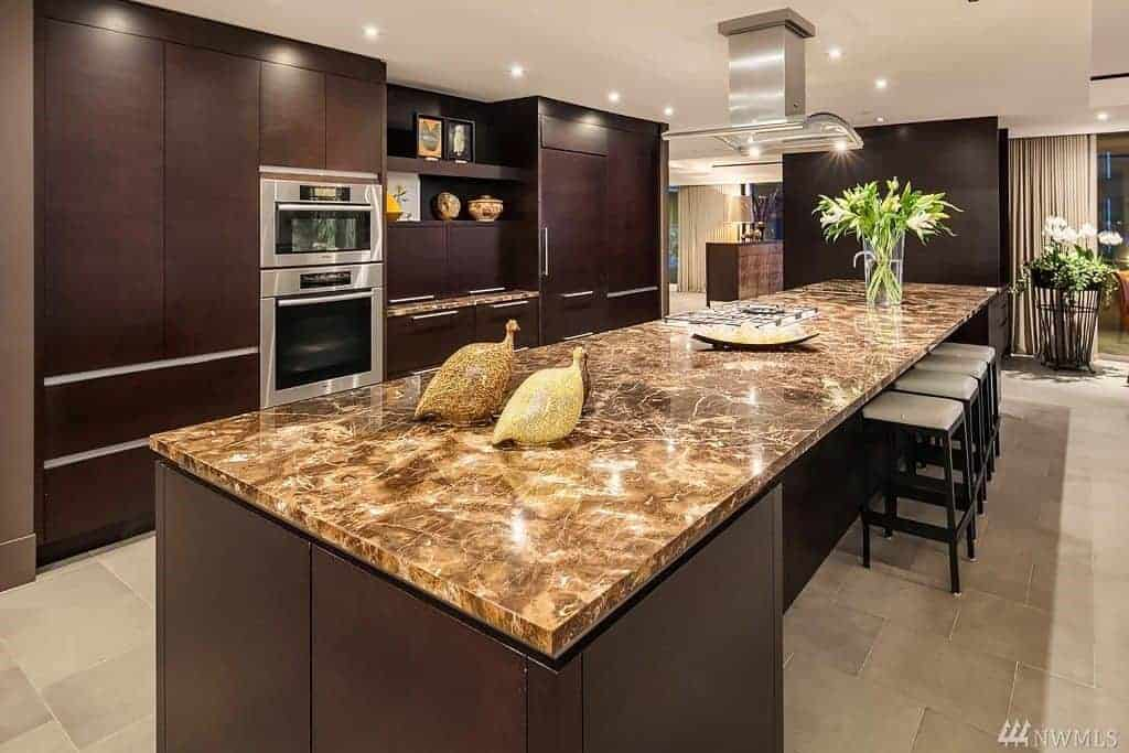 A single wall kitchen boasts a massive and long kitchen island with a stunning countertop and has space for a breakfast bar.