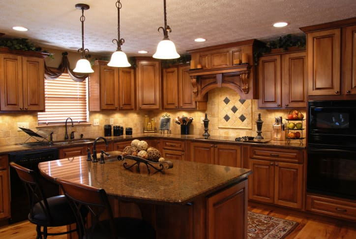 Brown L-shaped kitchen featuring wooden kitchen counters and cabinetry, along with a small center island featuring a granite countertop lighted by three pendant lights.