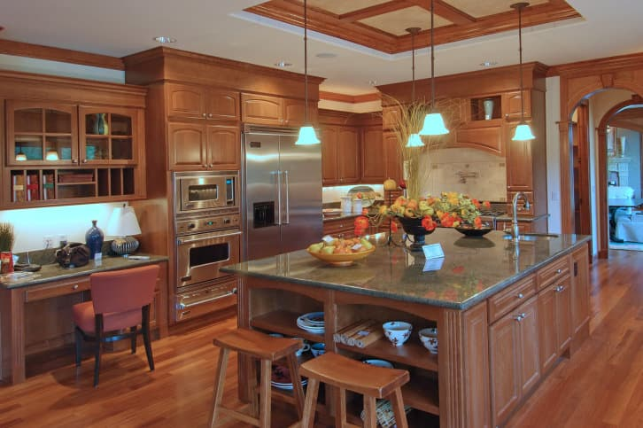 Brown L-shaped kitchen with a tray ceiling and hardwood flooring, along with a study desk below the built-in hanging cabinet. The kitchen also offers a large center island with a granite countertop.
